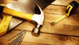 Image of a hammer, saw, nails and metal tape measure on a wooden floor.