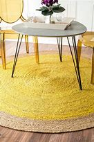 """Image of a circular rug on a wooden floor with a triangular shaped table and two """"Ghost"""" style chairs. The"""