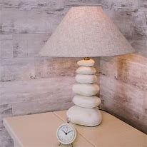 Image of a lamp on a table in the corner of a room. The lamp base is composed of a series of pebbles one on top of the other with a simple conical shade in a natural fabric.