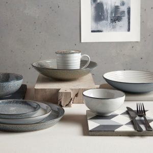 Image of grey stoneware crockery on a table. There are plates and bowls of different sizes and a table mat