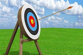 Image of an archery target in a field with an arrow in the bullseye