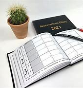 Image of a hotel reservations diary. The diary is open with a page marker and there is another black covered diary behind and a cactus in a pot next to it.
