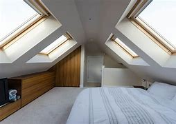 Image of a a bedroom in a converted loft which features velux windows. There is a double bed with built in storage opposite