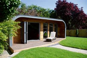 Image of an outdoor garden room. The structure has bifold doors plus additional full length windows and curved roof which overhangs. There is a sun lounger outside
