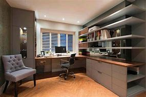 Image of a home office. There is a work surface positioned under a window with office style chair, shelving and storage to one side and an easy chair opposite