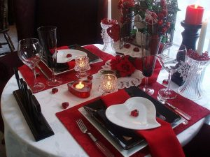 Image of a table set for Valentine's Day with white tablecloth, red placemats and heart shaped plates