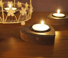 Image of two lit heart shaped wooden tea light holders on a table
