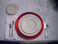 Image of a table place setting on a white table cloth. There is a red charger plate on top of which is a dinner plate and smaller plate both white with a silver rim. There is also cutlery and two wine glasses.