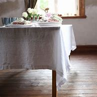 Image of a small dining table dressed with a plain white linen cloth. There are two place settings on the table and a vase of white flowers in the centre