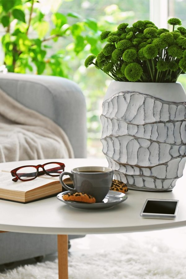 Image of a coffee table in front of a sofa. There is a vase with a plant in it on the table next to a book with glasses on it and a cup and saucer
