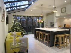 Image of a kitchen diner with a central island and a yellow sofa to the left. The kitchen units are grey with a white worktop. There are bifold doors at the back and a skylight over the sofa