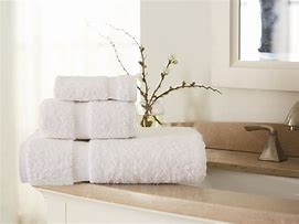 Image of fluffy white towels on the side of a washbasin