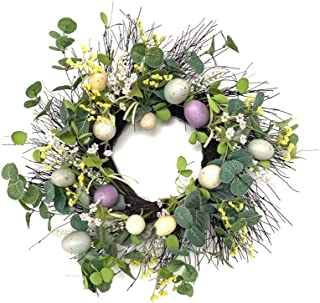 Image of decorative wicker wreath decorated with green foliage, yellow flowers and painted eggs