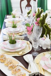 Image of a dining table set for Easter with green rabbits down the centre. Each place setting has a little basket with handle and a small green plant in it. The are also vases with pink tulips