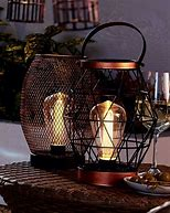 Image of two wire mesh outdoor lanterns with handles positioned on a table.