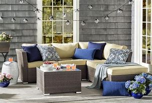 Image of an outdoor seating area with L shaped settee. The settee is dressed with cushions and throws