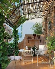 Image of a balcony with wrought iron garden bench small table and chairs. There is a slatted awning overhead and lots of greenery