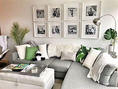 Image of a living room with a gallery wall of family photos. The photos are in black and white in white square frame