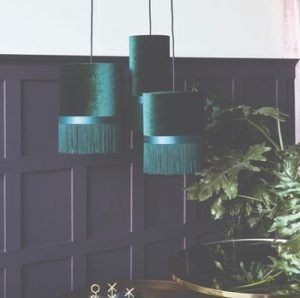 Image of a room with dark panelling and three ceiling lights with green velvet shades and deep matching fringing