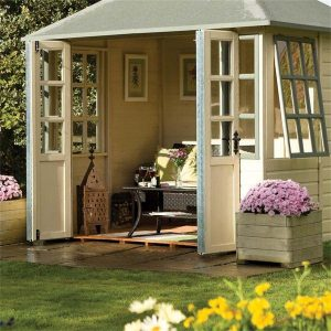 Image of a summerhouse painted in a pale stone colour. The doors (with glass windows) are open and there is a rattan sofa and coffee table inside. Next to the summerhouse is a wooden planter painted to match planted with flowers