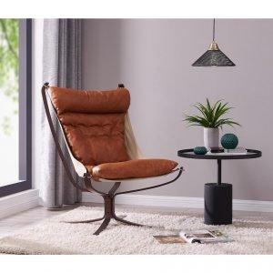Image of a modern style metal framed armchair with caramel coloured leather upholstery in the corner of a room by a window. Next to it is a side table with ceiling light above. On the table is a green plant in a pot .