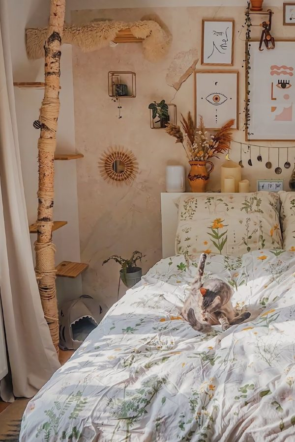 Image of a cottage style bedroom featuring a bed dressed with floral bed linen. There are pot plants ad pictures on on the wall
