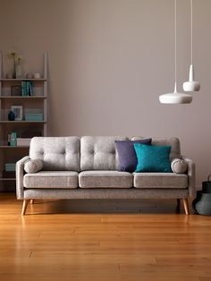 Image of a grey button back G Plan sofa against a grey wall . There is a bookcase to the left and white ceramic lamps hanging from the ceiling to the right. There are two blue cushions on the sofa