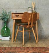 Image of a small wooden desk against a wall with a chair positioned in front