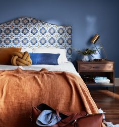 Image of a bed with a curved headboard upholstered in a patterned fabric. The bed is dressed with a white duvet and there is a terracotta coloured throw across the bottom and orange and blue cushions at the top.