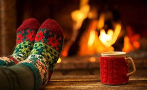Image of a person with their feet up in front of a fire. Just the feet are shown and they are encased in thick patterned socks. There is a mug next to them with a red knitted mug sleeve.