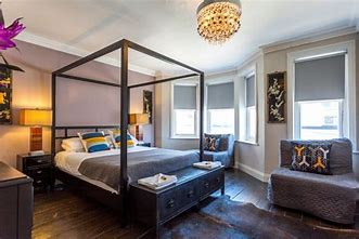Image of a boutique hotel style bedroom with simple four poster bed. The room is beautifully decorated in neutral decor with colourful cushions.