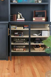 Image of cupboard built in to an alcove. Inside are shelves neatly stocked with board games and games consoles