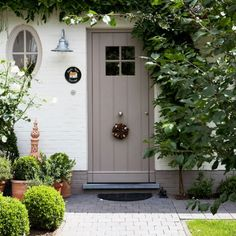 Image of the front of a property  showing a smart front door painted in a pale stone colour. There are plants either side
