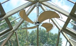 Image of a conservatory roof with a ceiling fan/light. The fitting comprises four arms and the blades have a metal frame with canvas insert resembling a sail.