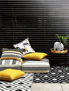 Image of an outdoor space with slatted screen. On the ground are a mixture of cushions in a colour palette of white black and ochre and varying styles. Some are intended for sitting on and others to go on chairs. Ther eis a metal topped side table with hairpin legs alongside