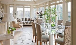 Image of a large conservatory with dining table and chairs and sofe