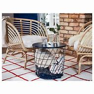 Image of two rounded rattan armchairs in a conservatory. They have white seat cushions. In between them is a a wire basket style side table