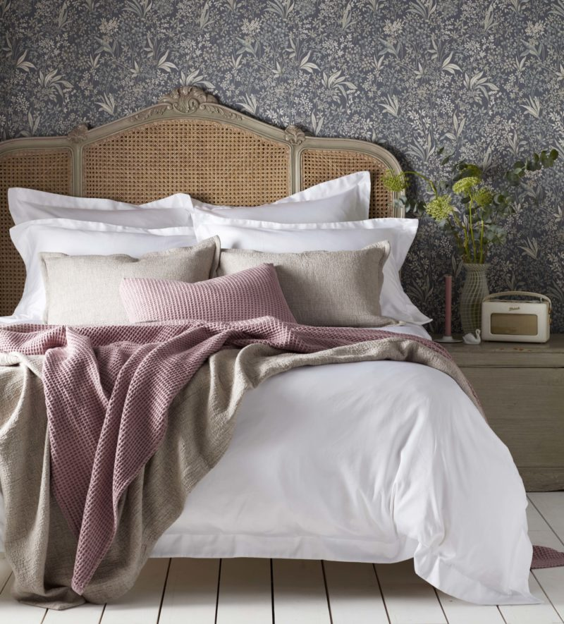Image of a bedroom. There is a botanical wallpaper behind the bed with a curved rattan headboard. The bed is dress with with bedding and a selection of cushions and throws in soft pink and natural colours.