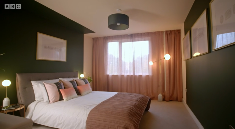 Image of a bedroom. The wall behind the bed has a panel painted to frame the bed painted in dark green. The panel is continued out across the ceiling for a short distance to give the effect of a canopy.