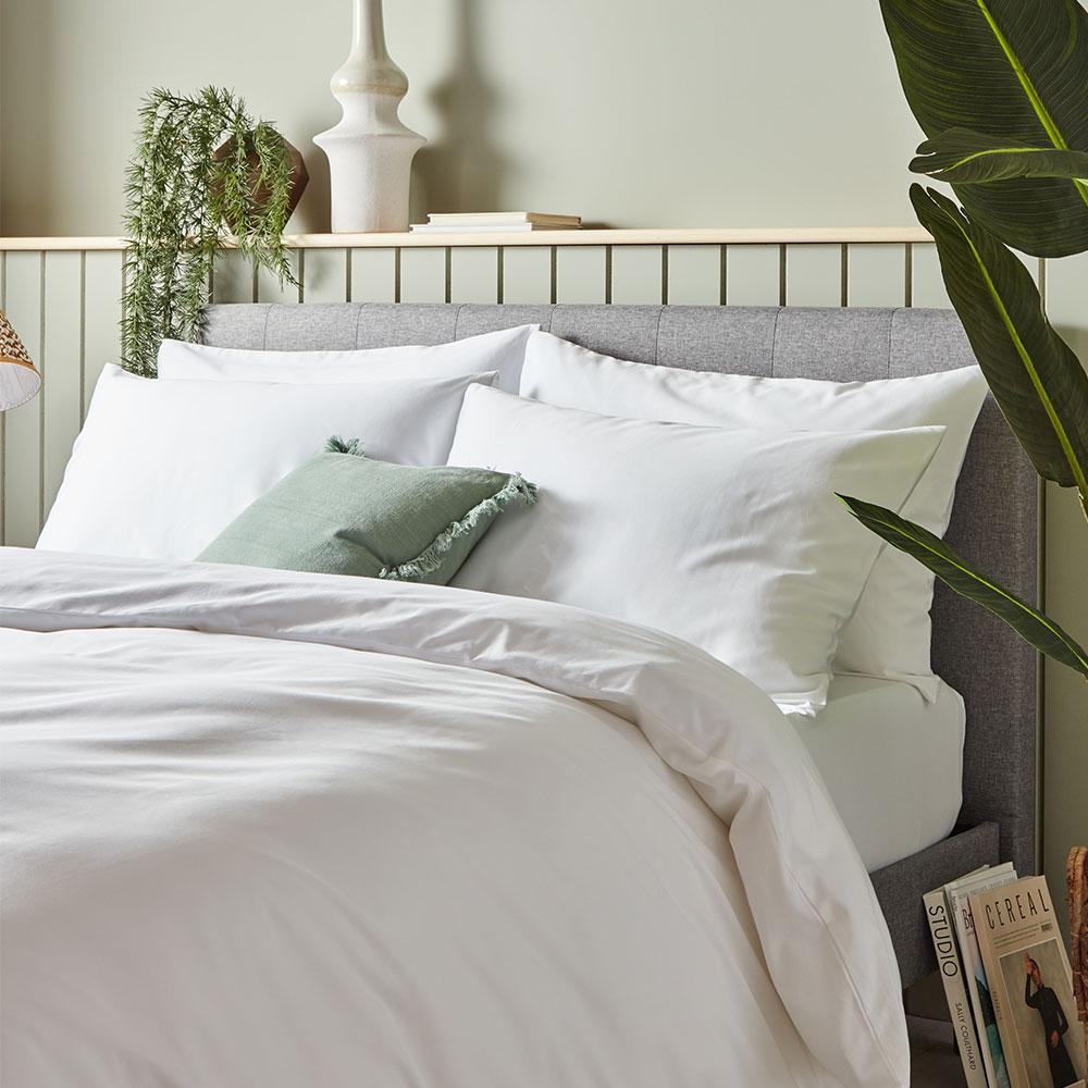Image of a bed with white bedding. The bed is placed against a half paneled wall. The paneling is built out so as to create a shelving area on which there is a plant, a vase and some books