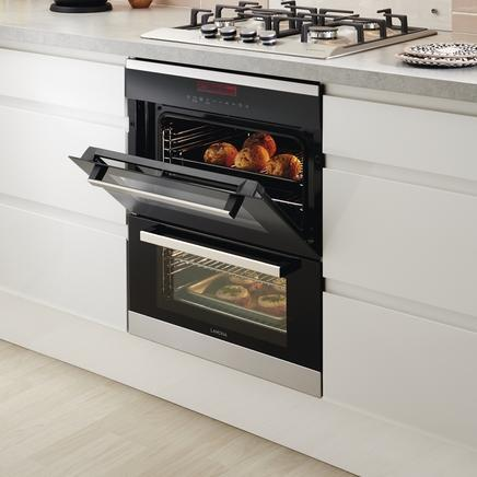 Image of an under counter built in double oven set in a white unit. The door of the top oven is open and shows buns being baked.