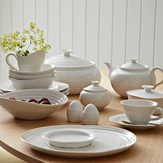 Image of a set of white ribbed crockery on a table. The set includes teapot, plates, bowls, cups and saucers butter dish and sugar bowl.