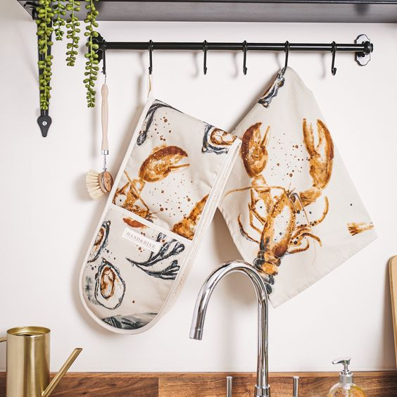 Image of a wall in a kitchen. There is a metal bar with hooks from which are hanging a tea towel and oven gloves with a seaside design