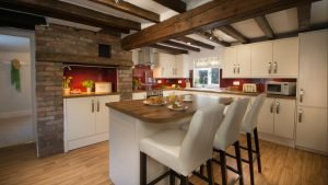 Image of a country kitchen with beams. There is an island with wooden worktop and upholstered bar stools