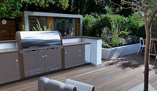 Image of an outdoor kitchen on a decked area. It is backed by a low white painted wall. The central element is a barbeque with sink and prep area to either side