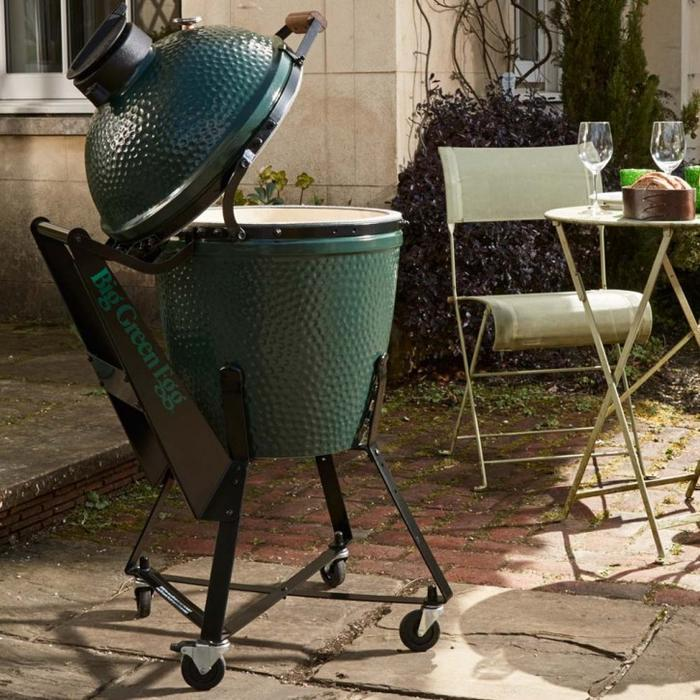 Image of an egg shaped barbeque which is on wheels. It is positioned on a patio next to a bistro style table and chairs