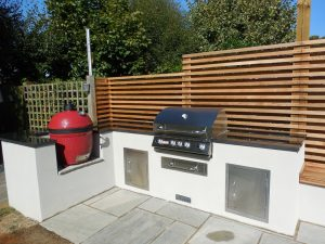 Image of an outdoor kitchen on a patio. It includes a built in egg style barbecue and traditional barbeque with storage