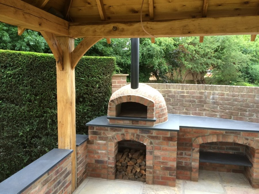 Image of a pizza oven in the corner of a patio area under a timber roof. It is built from brick with a storage area for logs underneath