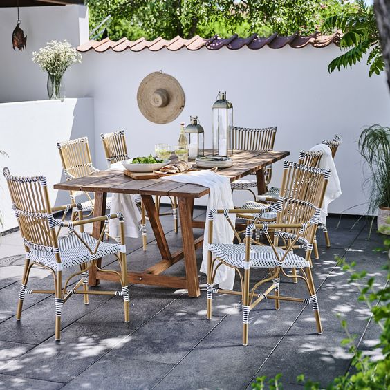 Image of an outdoor dining area  with wooden table with plank style top and rattan chairs