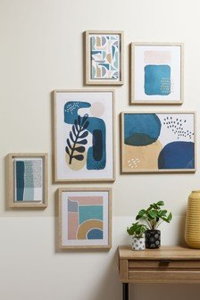 Image of a collection of abstract art works in pastel shades in pale wooden frames on a white wall. There is a wooden table to the right below on which are small green plants in pots and a yellow vase